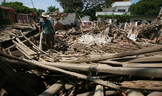 man stands in ruins of house following Mexico earthquake