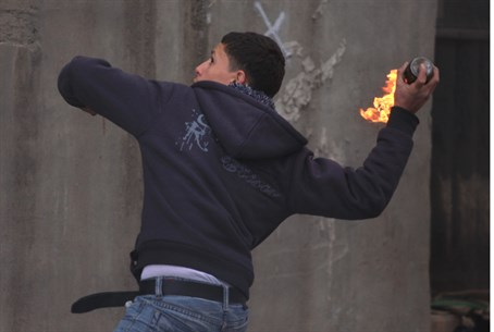 Arab youth hurls a firebomb during anti-Israe