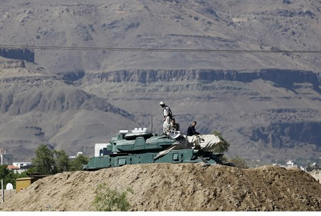 Houthi fighters sit on a tank in Yemen