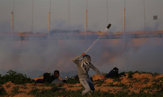 Demonstrator hurls rocks at Israeli troops on Gaza border